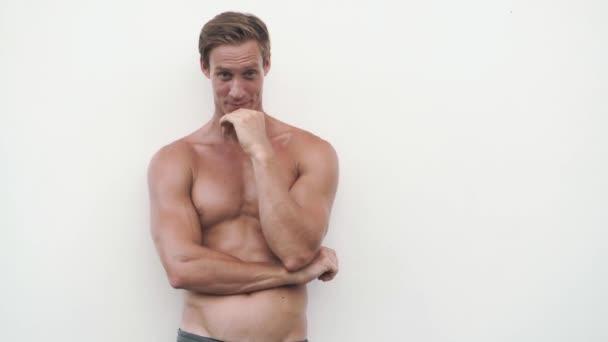 mladý muž s holým trupem vykazuje pozitivní emoce ve studiu