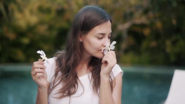 brunette lady sniffs plumeria flower at tropical resort
