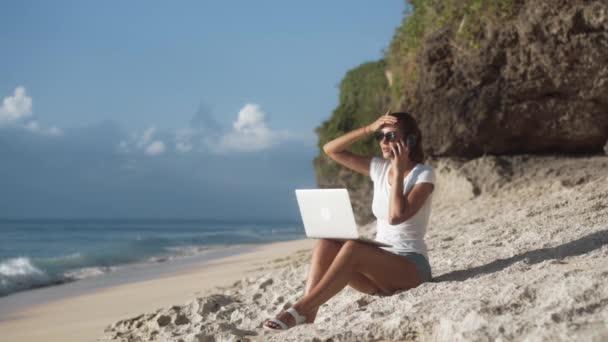 Nő szabadúszó napszemüvegben dolgozik a strandon laptop és beszél telefonon