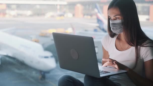 Woman in protective medical mask uses laptop for work at airport, COVID-19