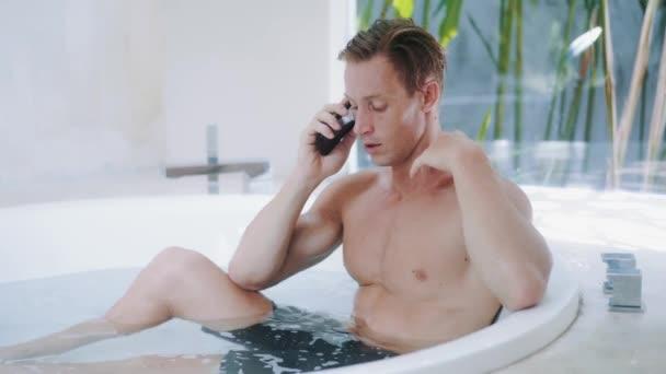Muskulöser blonder Mann spricht auf Smartphone in Badewanne in Luxuswohnung