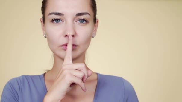 Portrét mladé ženy držící prst na rtech, gesto shhh, ticho