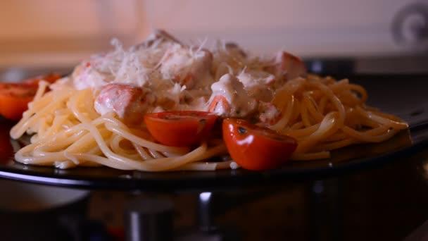 Putting parmesan cheese on spaghetti