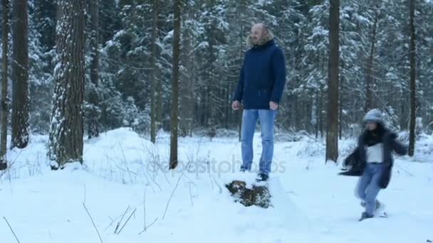Man in the woods on a stump, throwing snowballs. Jumping from the stump