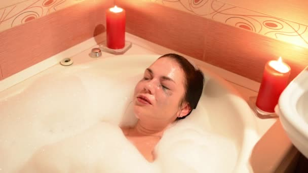 Krásná mladá žena relaxační v jacuzzi vířivka spa resort, romantické svíčky pozadím. Ponoří do pěny, výkřiky a smích