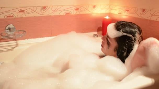 Krásná mladá žena relaxační v jacuzzi vířivka spa resort, romantické svíčky pozadím. Ponoří do pěny, výkřiky a smích.