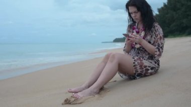 brunette girl sitting on a beach with a phone. girl smokes