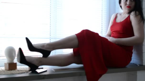 Dívka v červených šatech sedí na okenním parapetu