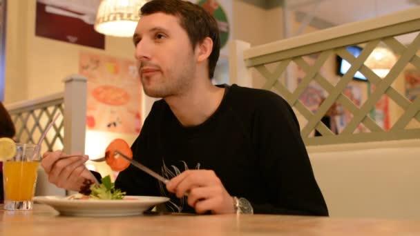 ein Mann sitzt in einem Restaurant und isst Salat