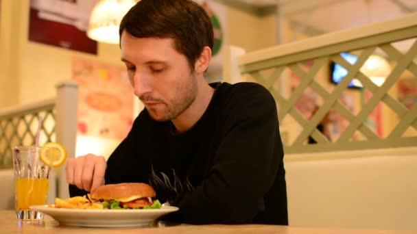 ein Mann hat einen Burger im Restaurant und trinkt Limonade