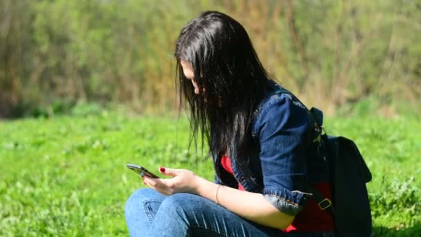 Teenage girl text messaging on cell smart phone in park