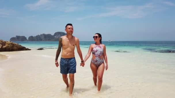A couple in love walks on a beach with azure water on a desert island