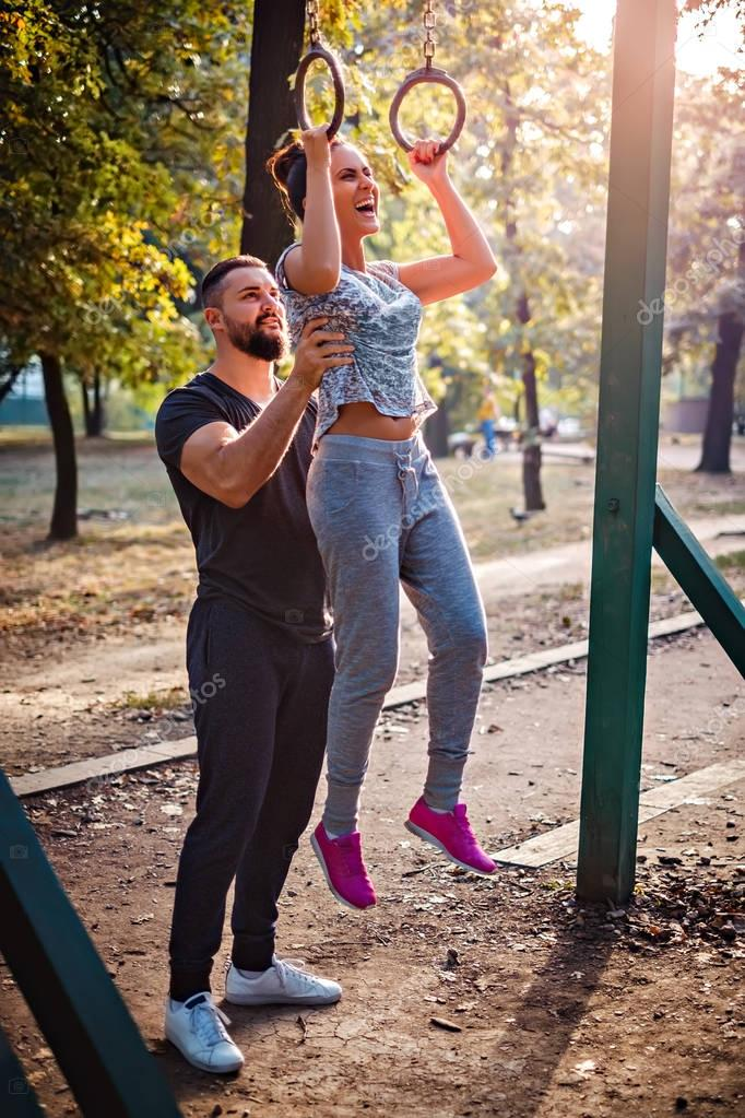 Man helping girl to do pull ups on rings
