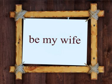 Wood frame on wooden background. The inscription, be my wife