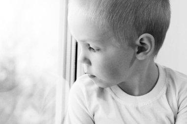 Adorable little blond kid boy sitting near window, so sad