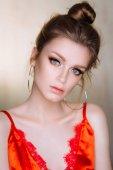 Studioporträt einer schönen jungen Frau, die in roten Dessous posiert
