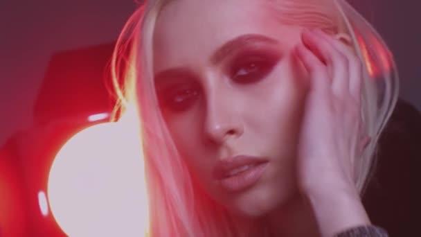 Nádherná mladá žena s smokey oči make-up pózuje
