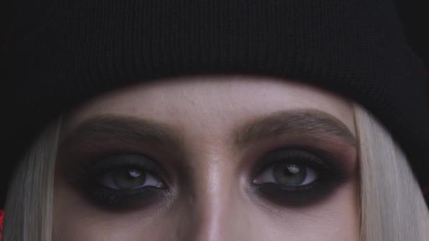 Nahaufnahme der wunderschönen jungen Frau mit Smokey Eyes Make-up auf dunklem Hintergrund