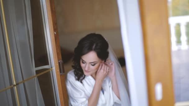 Krásná nevěsta nádherná bruneta ráno. Pózuje anf uvedení na luxusní náušnice ráno