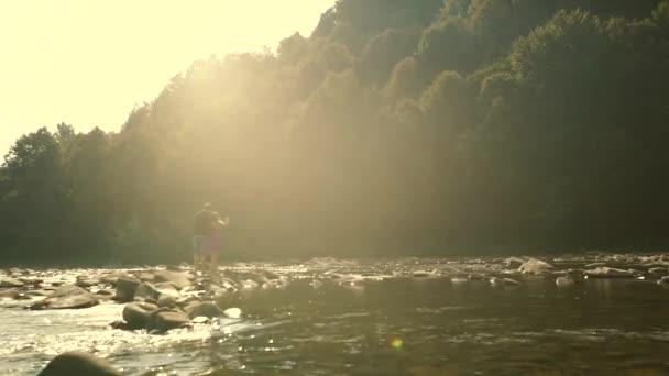 Coppia di innamorati camminano lungo le rocce del fiume