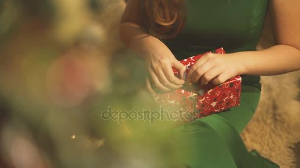 Dívka rozbalí novoroční dárek