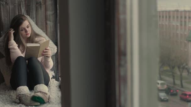 Gyönyörű fiatal nő ül az ablakban és olvasni egy könyvet