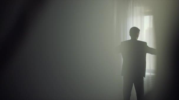 A fiatalember visel öltönyt, az ablak előtt