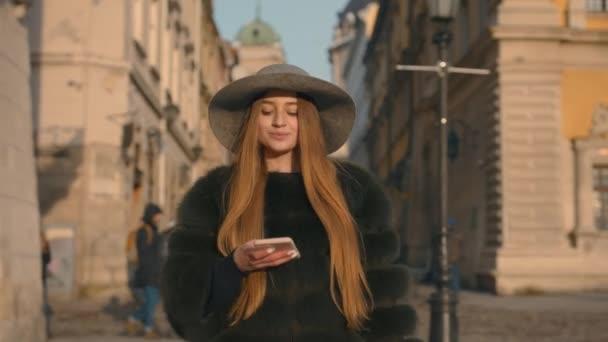 Junge Frau mit grauem Hut und langen Haaren kommuniziert per Smartphone
