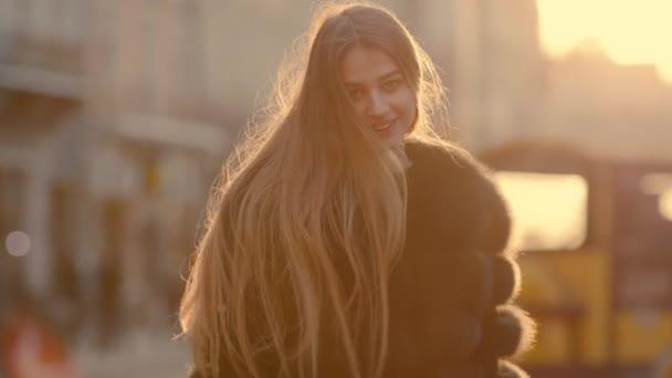 Atraktivní mladá dáma se řítí v centru města, otáčí se na kameru a usmívá se