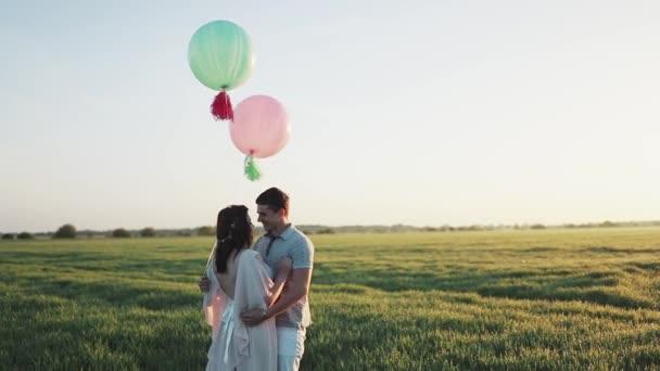 Paar mit Heliumbällen, die in einem Apfelgarten spazieren und sich bei Sonnenaufgang an den Händen halten. In Zeitlupe gefilmt