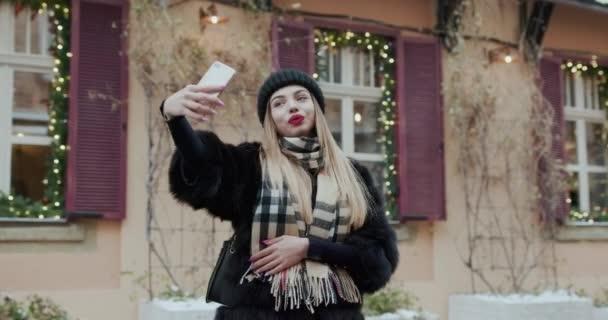 Porträt schöne Mädchen macht Selfie-Foto auf dem Smartphone auf der Straße. sexy Frau fotografiert in luxuriöser Kleidung im Freien. Frau macht Selbstporträt in der Nähe der Stadtstraße.