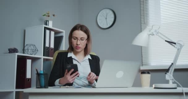 Sebevědomá podnikatelka pracující na laptopu ve své moderní kanceláři. Stylová krásná žena dělá důležitou práci.