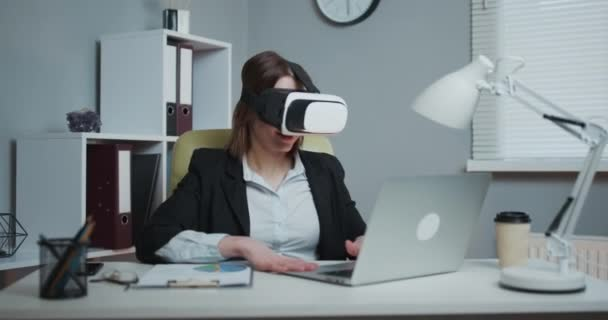 Business woman wearing virtual reality glasses in office. Young girl using VR goggles in office. Pretty woman working in augmented reality at workplace.
