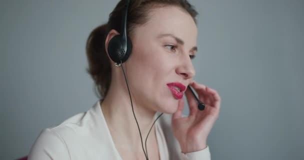 Call-Center-Mitarbeiterin freut sich über Gespräch mit Kunden, die per Headset Fragen online beantworten, netter höflicher Call-Center-Agent mit Kopfhörer im Gespräch mit Klient im Büro.