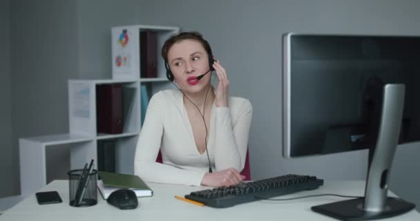 Call center operator is tired of talking to people asking stupid questions. Young customer service representative at work. Young female worker productively operating at call-centre