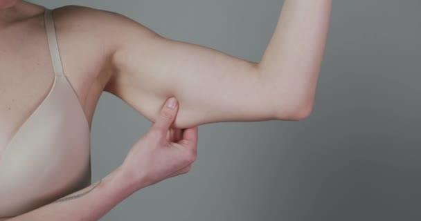 Koncept hubnutí. Buclatá žena štípání horní části paže tuk izolované na šedém pozadí. Detailní záběr kavkazské ženské kontroly rukou Flabby Skin. Kontrola těla, čas jít na dietu