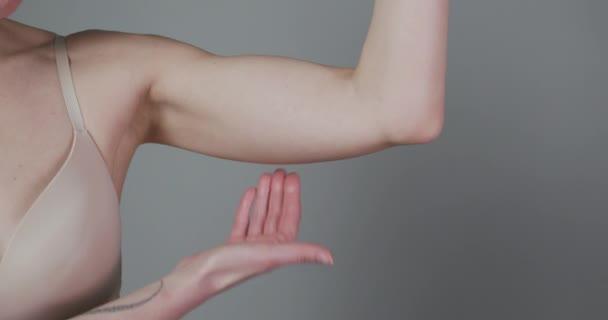 Buclatá žena štípání horní části paže tuk izolované na šedém pozadí. Detailní záběr kavkazské ženské kontroly rukou Flabby Skin. Ovládání těla, Čas jít na dietu a hubnutí koncepce