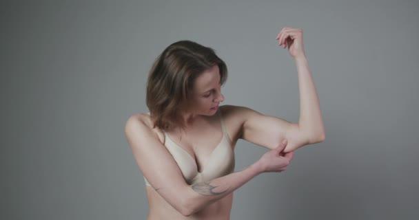 Koncept hubnutí. Žena štípání horní části paže tuk. Detailní záběr kavkazské ženské kontroly rukou Flabby Skin. Kontrola těla. Čas jít na dietu