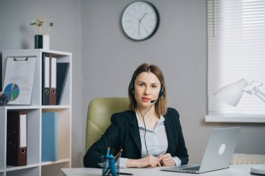 Woman in Headphones Holding Paper Financial Report talk at Webcam make video call in office, business coach looking at camera speak show statistics explain marketing strategy for client