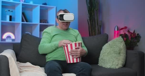 Ein älterer Mann aus dem Kaukasus, der ein Video mit einem Virtual-Reality-Headset anschaut, sitzt auf einem Sofa und isst Popcorn in einem Raum