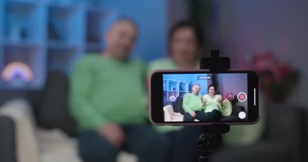 Ältere alte Blogger vloggers Paar im Gespräch mit der Kamera Aufzeichnung Blog vlog zu Hause, freundlich lächelnd ältere Familie Videotelefonie über Webcam sitzen auf dem Sofa kommunizieren online