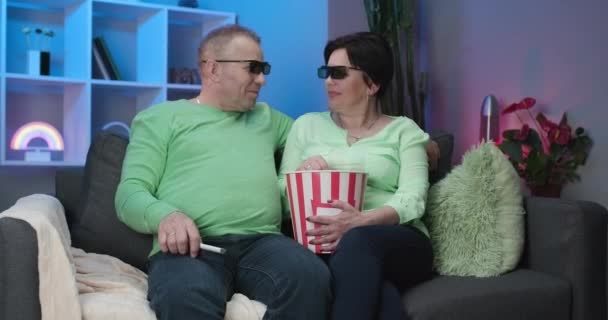 Senior couple Wearing 3d Glasses and eating popcorn. Older man and woman watching tv together, sitting at home on sofa, happy couple. People with relaxation, old age, retirement, senior family concept