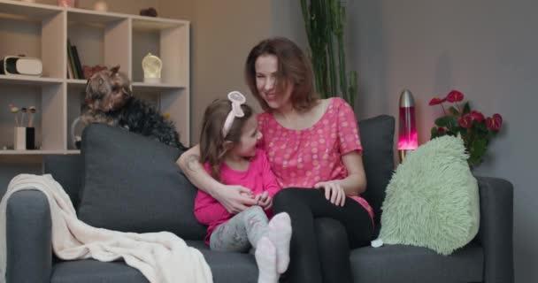 Žena a její dcerka sedí na gauči a dívají se na komediální film na televizi a smějí se