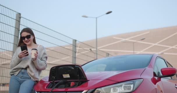 Nabíjení elektromobilu. Žena stojí s telefonem v blízkosti svého elektrického auta a čeká, až vozidlo nabíjí.