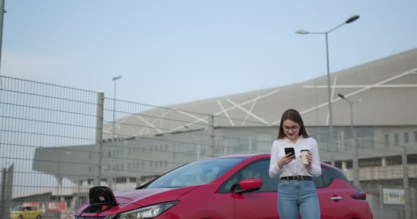 Girl using smart phone and waiting power supply connect to electric vehicles for charging the battery in car. Ecological car connected and charging batteries.