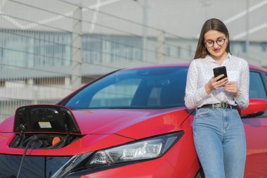 Ecological car connected and charging batteries. Girl using smartphone and waiting power supply connect to electric vehicles for charging the battery in car