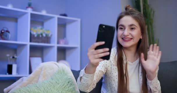 Fiatal lány blogger befolyásoló kezében modern okos telefon hullám kéz hello. Mosolygó vlogger lány nézi a mobil make video hívás, forgatás vlog selfie.