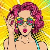 Wow il viso di pop art. Donna sorpresa sexy con capelli ricci rosa e bocca aperta tenendo gli occhiali da sole in mano con wow iscrizione nella riflessione. Fondo variopinto di vettore nel retro stile fumetto pop art.