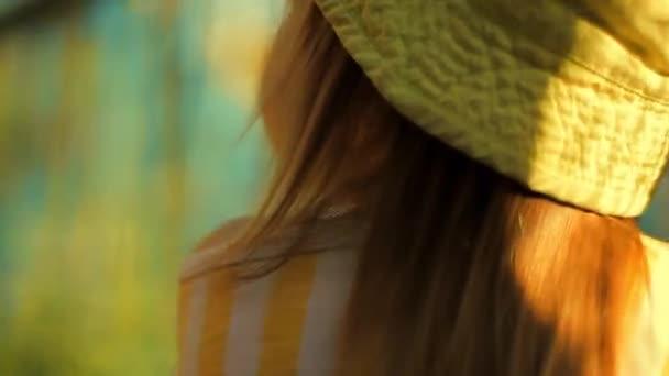 Pohled zezadu: malá krásná dívka v zeleném klobouku stojící poblíž zeleného pletiva oka a třese se a vypadá kolem