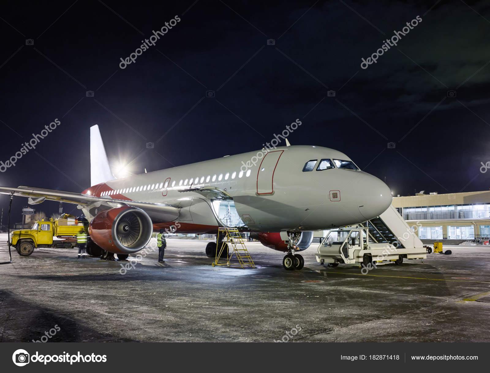 Ground Handling Passenger Airplane At Night Winter Airport Stock Photo